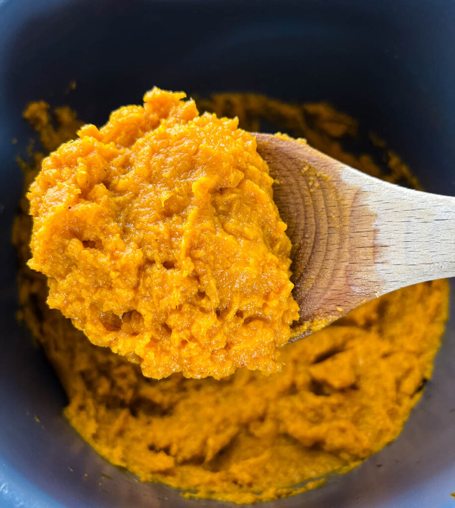 a wooden spoonful of mashed sweet potatoes
